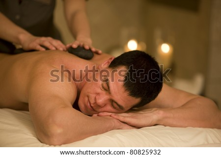 Close-up of man lying down in spa with hot stones on back. - stock photo