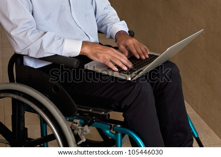 Close-up of man on wheelchair using laptop.