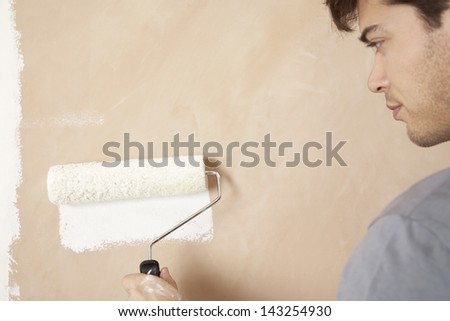 Close-up of man painting wall with paint roller - stock photo