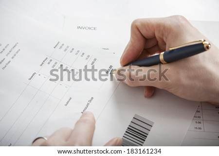 Close-up of man paying bills pen in hand