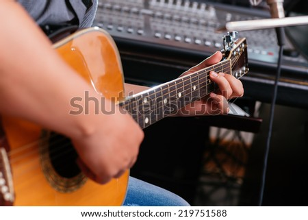 Close-up of man playing guitar - stock photo