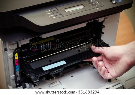 Close up of man puts toner in the printer - stock photo
