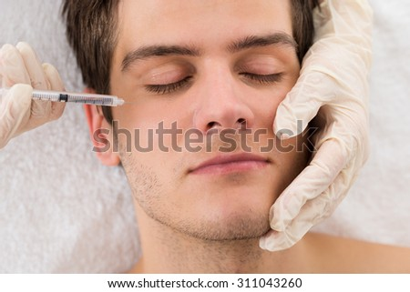 Close-up Of Man Receiving Wrinkle Treatment On Face In Beauty Clinic - stock photo