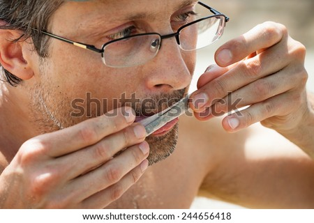 Close up of man rolling hashish joint. - stock photo