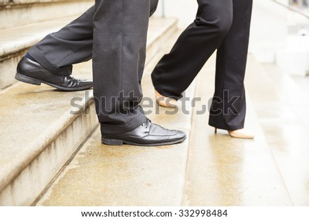 Close-up of man's and women's legs walking down an outdoor stone staircase together.