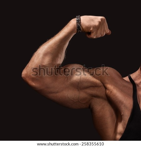 Close up of man's arm showing biceps. Isolated on a black background - stock photo