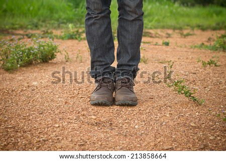 Close up of man's boots while hiking on trail in the mountains. - stock photo