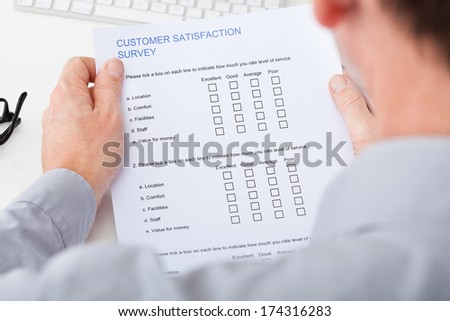 Close-up Of Man's Hand Filling Customer Survey Form
