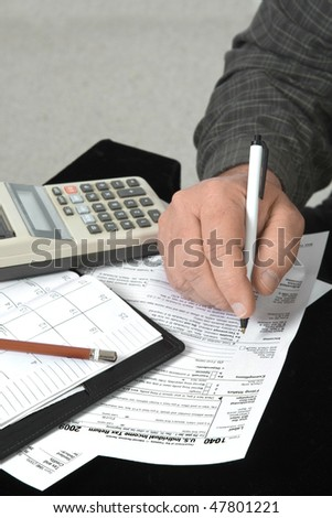 Close up of man's hand filling out income tax 1040 form. - stock photo