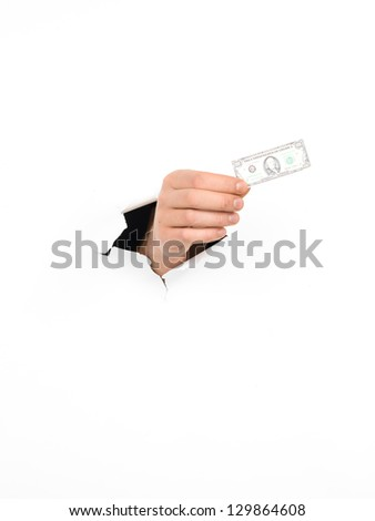 close-up of man's hand holding a miniature dollar banknote through a torn white paper, isolated - stock photo