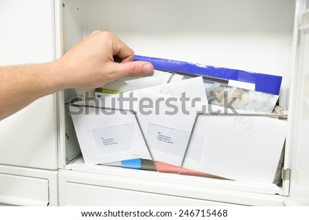 Close-up Of Man's Hand Taking Letter From Opened Mailbox - stock photo