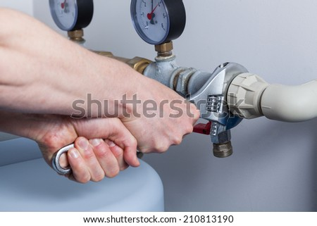 Close-up of man's hands during pipe repair