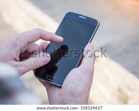 Close up of man's hands holding and using mobile smartphone