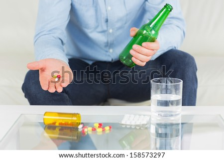 Close up of man showing pills and holding bottle in bright living room