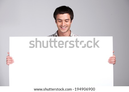 close up of man showing white board. guy showing empty space white placard  - stock photo