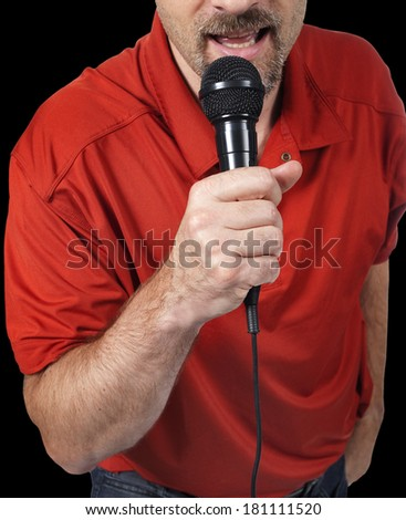 close up of man singing in a microphone isolated on black - stock photo
