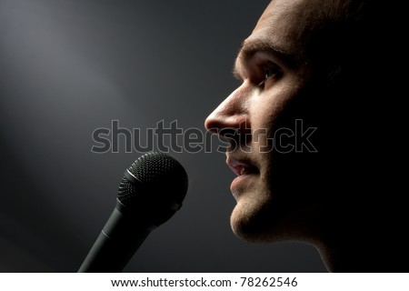 Close-up of man singing to microphone in dark