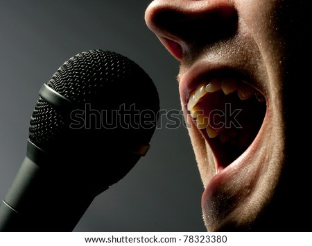 Close-up of man singing to microphone in dark - stock photo