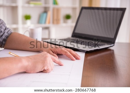 Close-up of man sitting at the table at home and drawing sketch. - stock photo