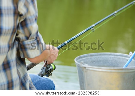 Close up of man sitting on pier with rod