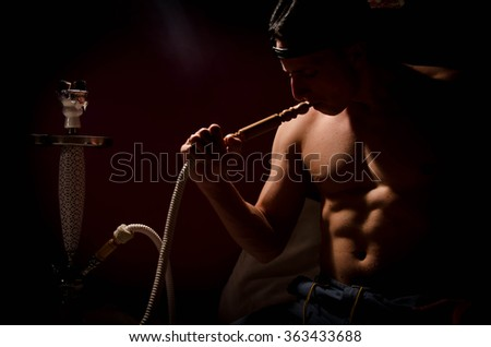 Close-up of man smoking traditional hookah pipe. man exhaling smoke on black background - stock photo