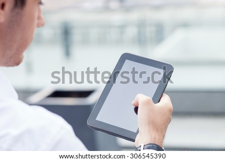 Close up of man using a tablet for his work. He is looking at the technology with concentration - stock photo