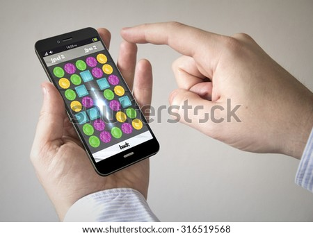Close up of man using 3d generated mobile smart phone with puzzle game on the screen. Screen graphics are made up. - stock photo