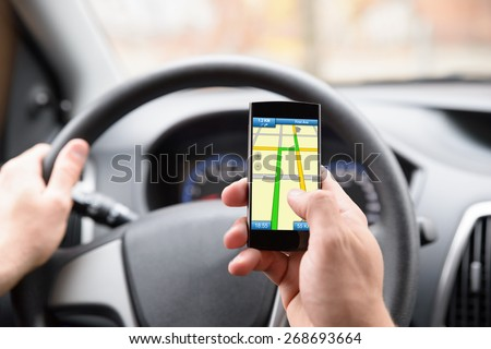 Close-up Of Man Using Gps Navigation In Cellphone While Driving Car - stock photo