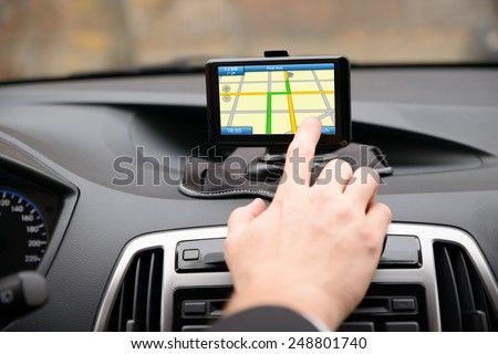 Close-up Of Man Using Gps Navigation System In Car - stock photo