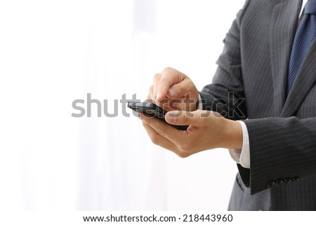 Close up of man using mobile smart phone isolated on white background - stock photo