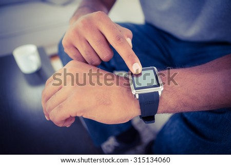 Close-up of man using smart watch at home
