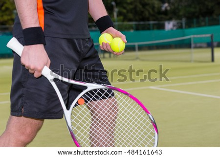 Close-up of man wearing a sportswear holding tennis balls and  racket during the match on a court outdoor in summer