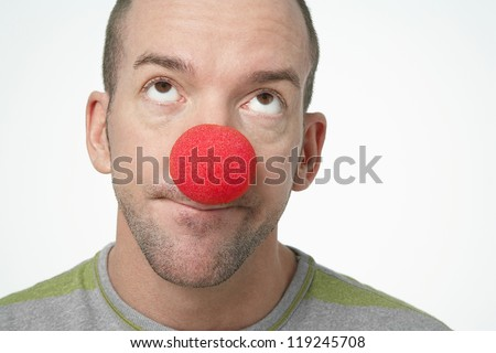 Close-up of man wearing clown nose looking upwards isolated over white background - stock photo