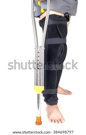 Close-up of man with plaster on leg holding crutch.