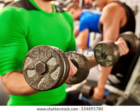 Close up of man working his arms with dumbbells at gym. He lifting dumbbells. - stock photo