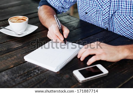 Close-up of man writing something in a notepad - stock photo