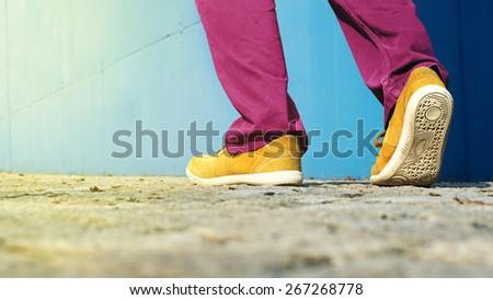 Close up of man yellow shoes walking alongside blue wall. - stock photo