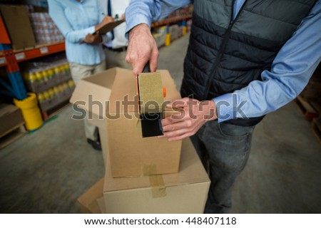 Close up of manager hands taping up a cardboard box in a warehouse