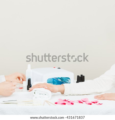 Close up of manicure beauty process. Smoothy hands of female beautician manicurist painting fingernails of woman using hybrid gel acrylic polish.