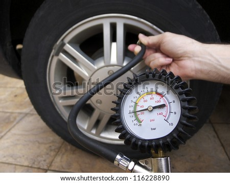 Close-up of manometer and man hands checking tyre pressure with gauge. - stock photo