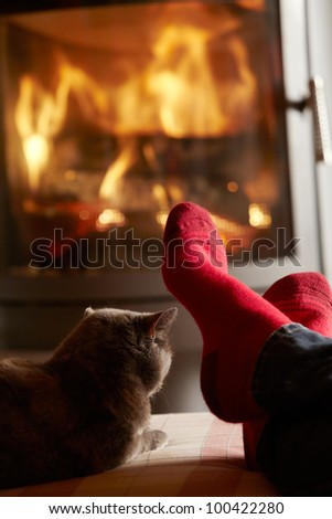 Close Up Of Mans Feet Relaxing By Cosy Log Fire With Cat - stock photo