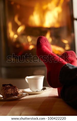 Close Up Of Mans Feet Relaxing By Cosy Log Fire With Tea And Cake - stock photo