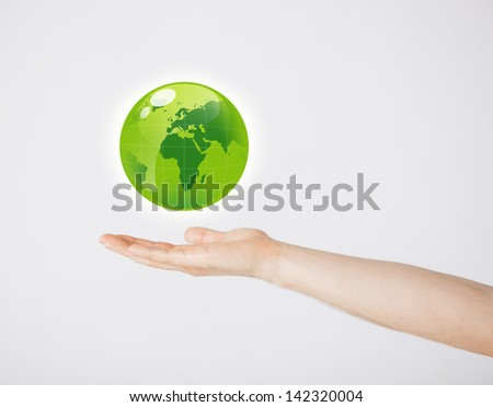 close up of mans hand holding green globe - stock photo