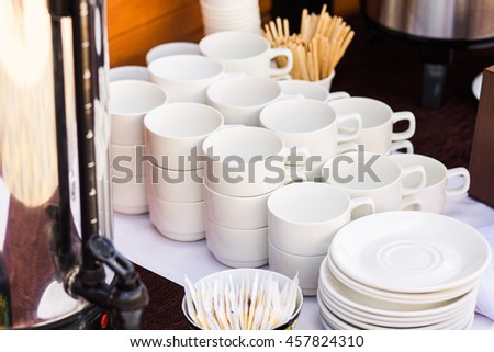 Close up of many empty clean white cups and small plates for coffee or tea and desserts in hotel or restaurant. Coffee brake in office.