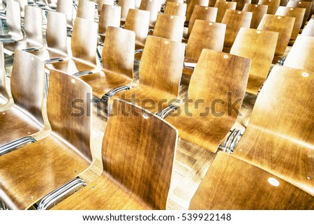 Close-up of many wooden chairs in rows