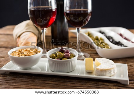Close-up of marinated olives with glasses of wine on table