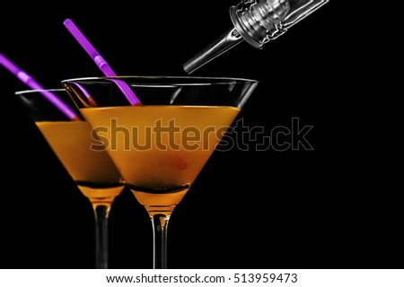 Close-up of martini with a straw on black background