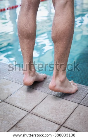 Close up of masculine feet at the edge of a pool - stock photo