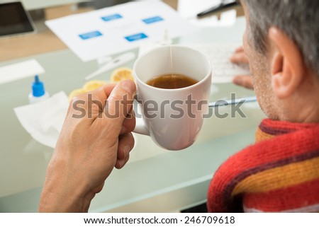 Close-up Of Mature Businessman Holding Cup Of Tea At Office - stock photo