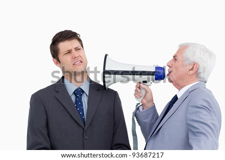 Close up of mature businessman with megaphone yelling at colleague against a white background